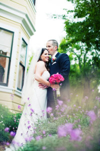 Perry House bride and groom pose front with purple and pink flowers