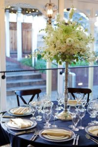 Perry House formal plated table with tall centerpiece blue linens and champagne napkins