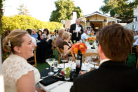 Perry House toasting in the garden at dinner with guests laughing with black napkins and orange flowers